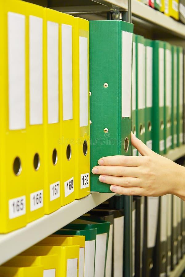 Pastas de arquivos amarelas e verdes no arquivo e na mão humana fotografia de stock royalty free