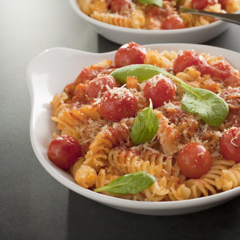Pastas de Fusilli con los tomates de cereza foto de archivo