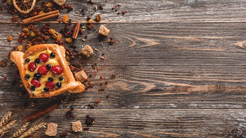 Pastas de hojaldre hechas en casa deliciosas para el desayuno con las bayas y la crema en la tabla de madera Foco selectivo, visi fotos de archivo