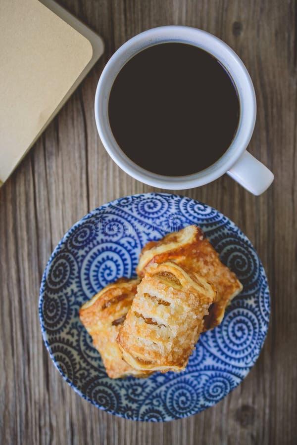 Pastas de hojaldre y taza de café frescas con el libro en blanco en el CCB de madera imagen de archivo libre de regalías