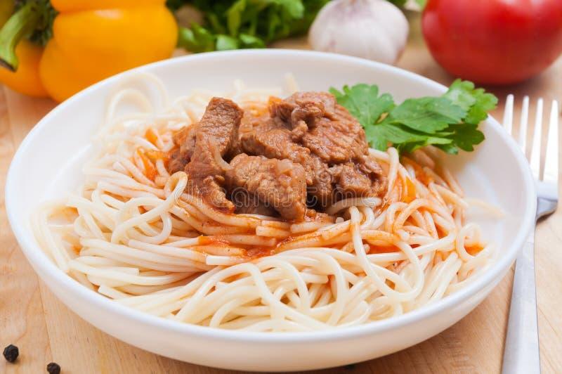 Pastas de los espaguetis con cocido húngaro de carne de vaca en una placa blanca en un tablero de madera Adornado con las verdura fotos de archivo libres de regalías