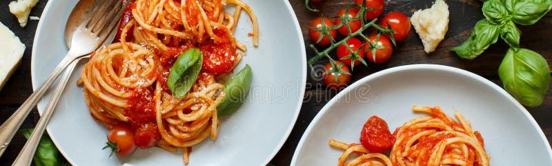 Pastas de los espaguetis con la salsa, la albahaca y el queso de tomate en una tabla de madera imagen de archivo libre de regalías
