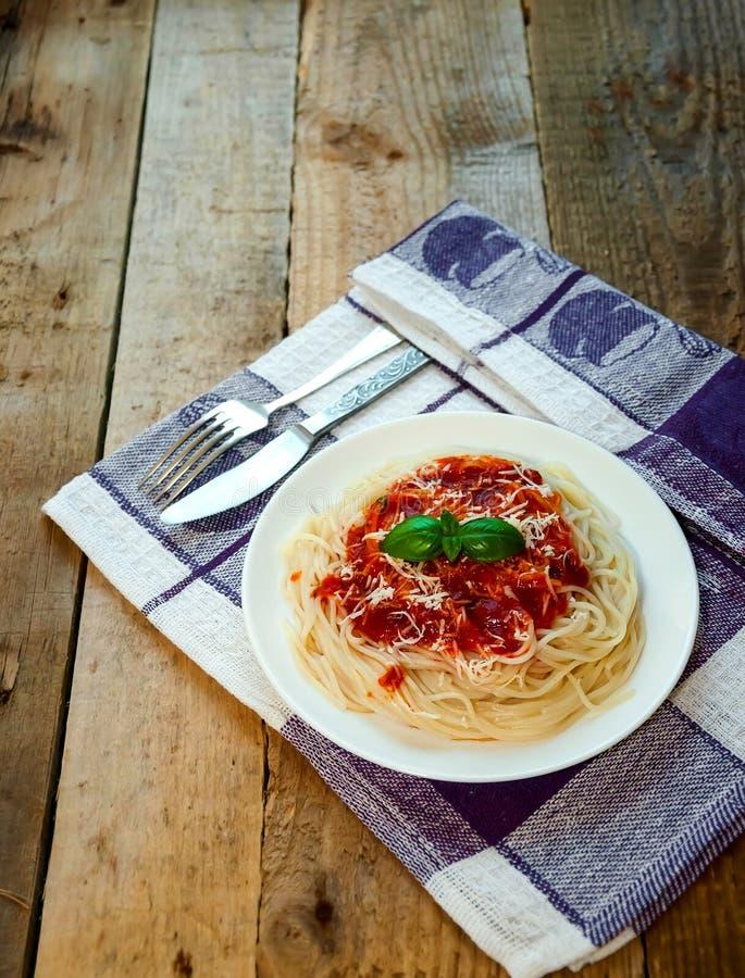 Pastas de los espaguetis con la salsa, el queso y la albahaca de tomate en la tabla de madera Alimento italiano tradicional imagen de archivo