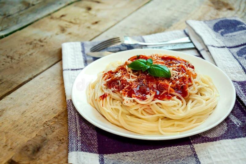 Pastas de los espaguetis con la salsa, el queso y la albahaca de tomate en la tabla de madera Alimento italiano tradicional foto de archivo