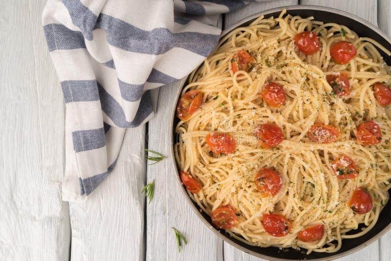 Pastas de los espaguetis con los tomates y el perejil en la tabla de madera imágenes de archivo libres de regalías