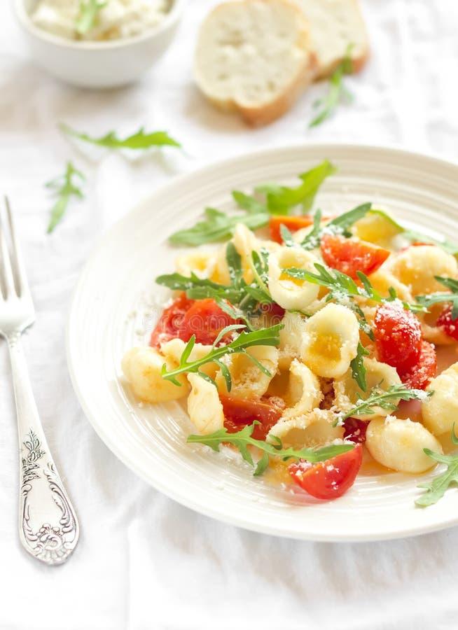 Pastas de Orecchiette con los tomates de cereza, el arugula y el parmesano fotos de archivo