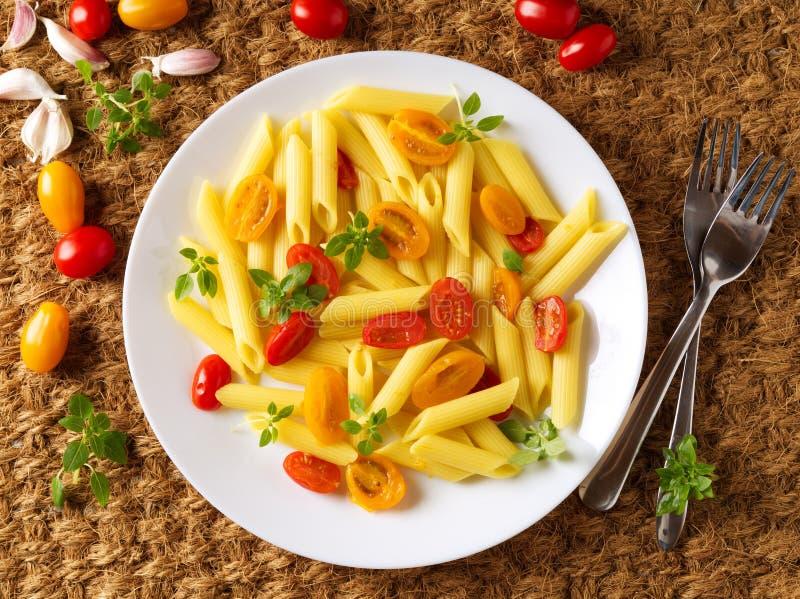 Pastas de Penne con los tomates amarillos y rojos adornados con albahaca en el fondo de la estera del sisal, comida de la dieta b fotos de archivo