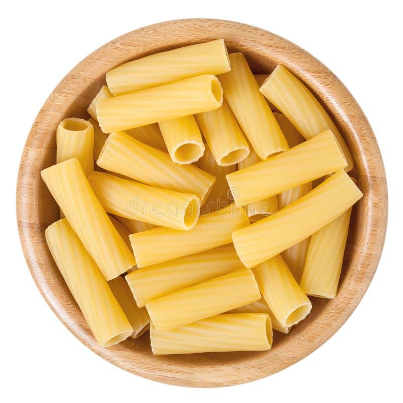 Pastas de Rigatoni en el cuenco de madera aislado en blanco imágenes de archivo libres de regalías