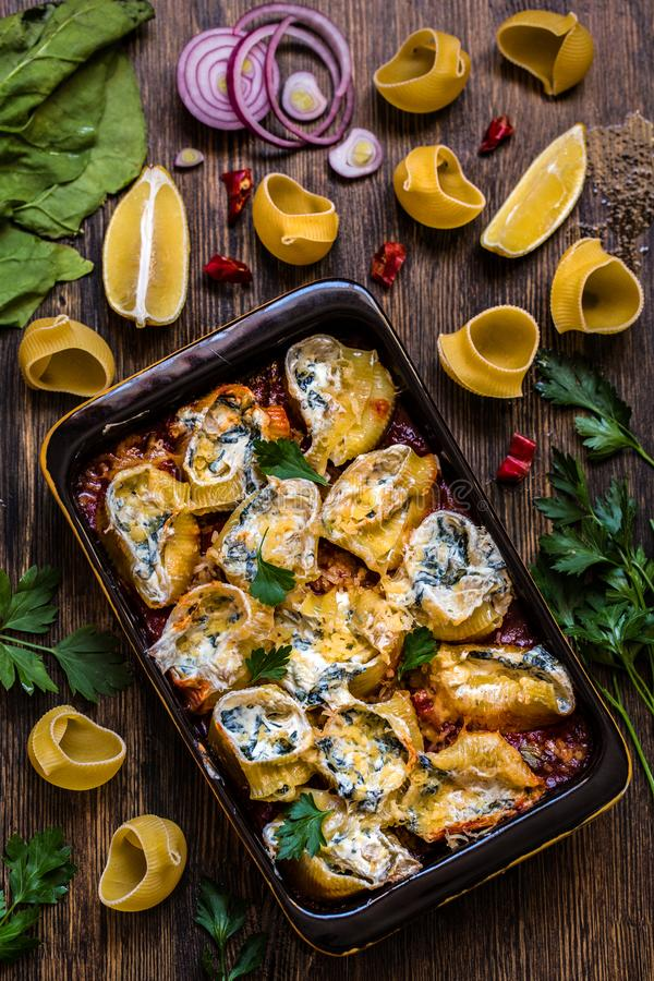 Pastas de Shell rellenas con la espinaca, queso cremoso, parmesano en salsa de tomate fotos de archivo libres de regalías