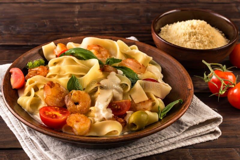 Pastas del Fettuccine con el camarón y los tomates en la tabla vieja fotos de archivo