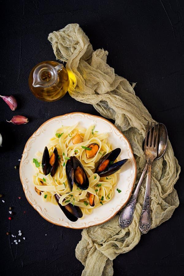 Pastas del fettuccine de los mariscos con los mejillones sobre fondo negro foto de archivo libre de regalías
