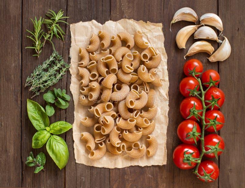 Pastas del trigo integral, verduras, hierbas y aceite de oliva fotos de archivo