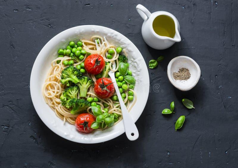 Pastas del Veggie Almuerzo vegetariano - espagueti con la col del bróculi, los guisantes verdes y los tomates de cereza en el fon imagenes de archivo