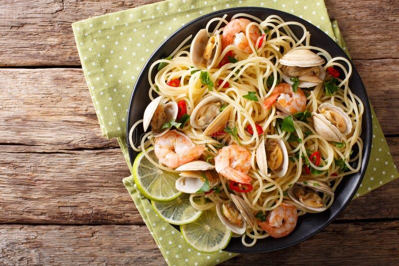 Pastas deliciosas de los espaguetis con las almejas, los camarones y cierre-u de los verdes fotografía de archivo libre de regalías