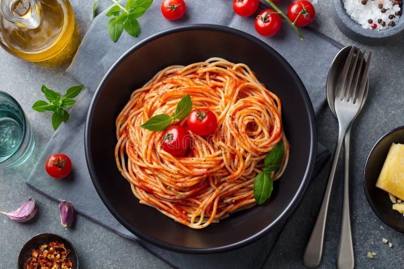 Pastas, espagueti con la salsa de tomate en cuenco negro en fondo de piedra gris Visi?n superior imagen de archivo