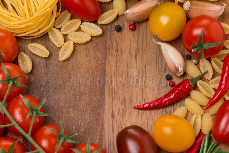 Pastas, especias y tomates de cereza en el tablero de madera imagenes de archivo