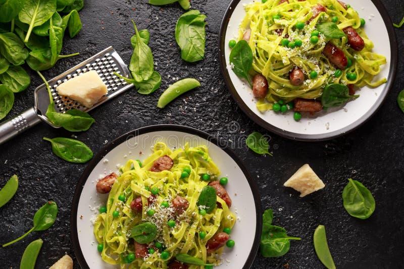 Pastas hechas en casa con los guisantes verdes, el pesto de la espinaca y las salchichas Queso parmesano Alimento sano Fondo imagen de archivo libre de regalías