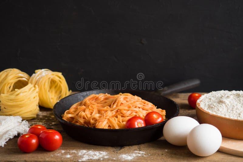 Pastas italianas cl?sicas tradicionales apetitosas con la salsa de tomate y albahaca en un sart?n negro en una tabla de madera Es imágenes de archivo libres de regalías