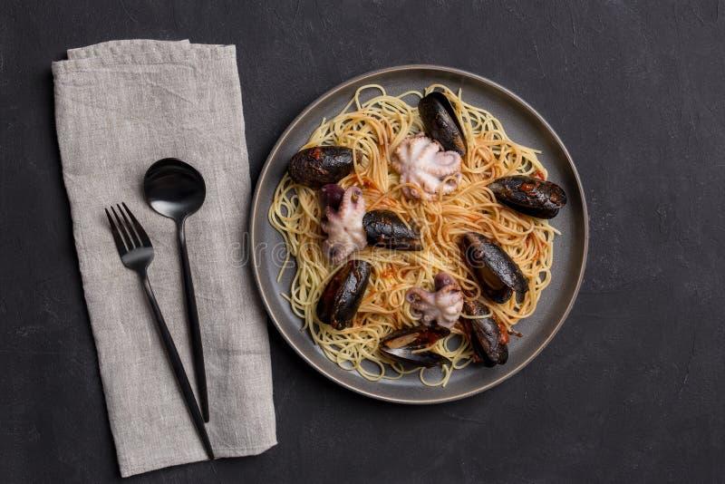 Pastas italianas con el pulpo y los mejillones en fondo gris imagenes de archivo