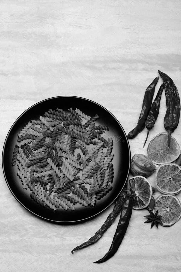 Pastas italianas en placa de cerámica negra con los ingredientes para cocinar imagen de archivo