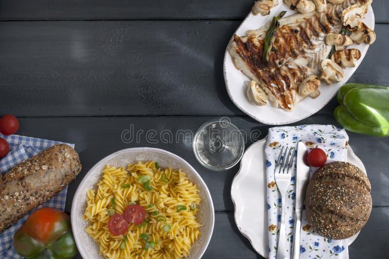 Pastas italianas, pescado asado a la parrilla, pan fresco en un fondo negro Cena italiana deliciosa Copie el espacio Endecha plan fotos de archivo libres de regalías