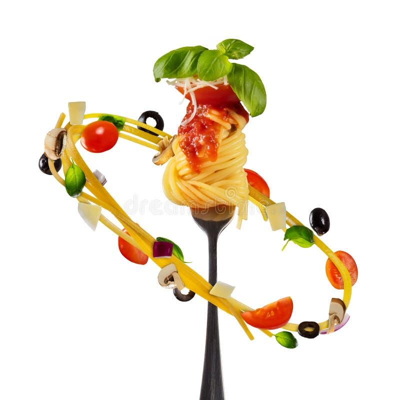 Pastas italianas que vuelan con la verdura y la bifurcación, aisladas en blanco imágenes de archivo libres de regalías
