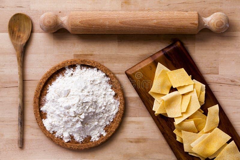 Pastas italianas Rodillo, harina, cucharón Superficie de madera foto de archivo libre de regalías