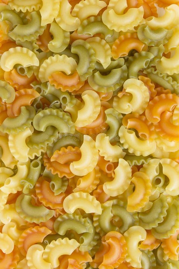 Pastas italianas verdes, amarillas, anaranjadas coloridas de la corona como textura creativa de la comida Fondo o textura de las  fotografía de archivo libre de regalías