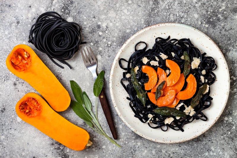 Pastas negras con calabaza moscada asada, queso parmesano y sabio frito Concepto negro y anaranjado de Halloween del partido de l foto de archivo