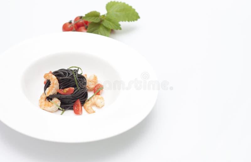 Pastas negras en el plato blanco foto de archivo