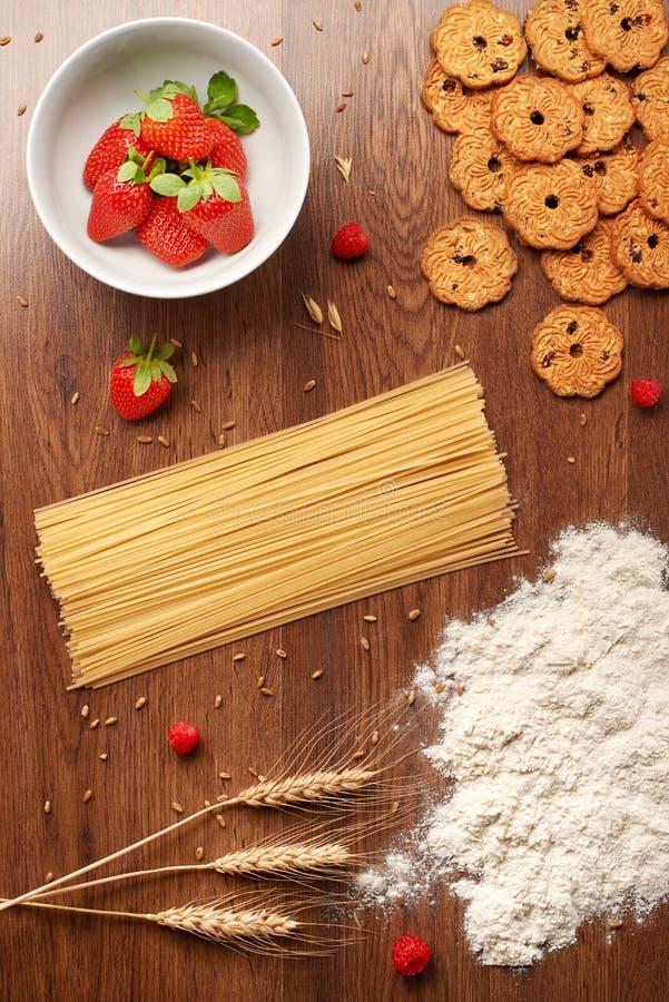 Pastas secas de los espaguetis, harina, trigo, galletas hechas en casa y bayas imágenes de archivo libres de regalías