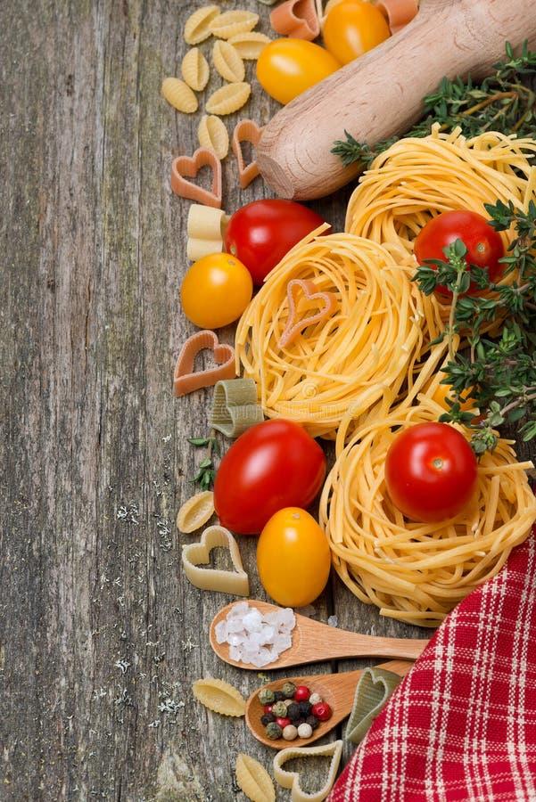 Pastas, tomates y especias en el fondo de madera, visión superior foto de archivo