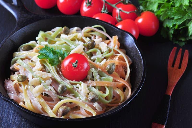Pastas vegetarianas con espinaca, zanahorias, las remolachas, el queso parmesano, las alcaparras, el aceite de oliva, los tomates fotografía de archivo libre de regalías