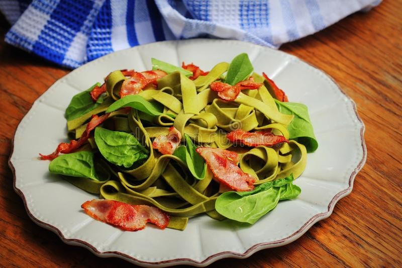 Pastas verdes de la espinaca con tocino chrispy en la tabla de madera Comida italiana gastr?noma fotos de archivo libres de regalías