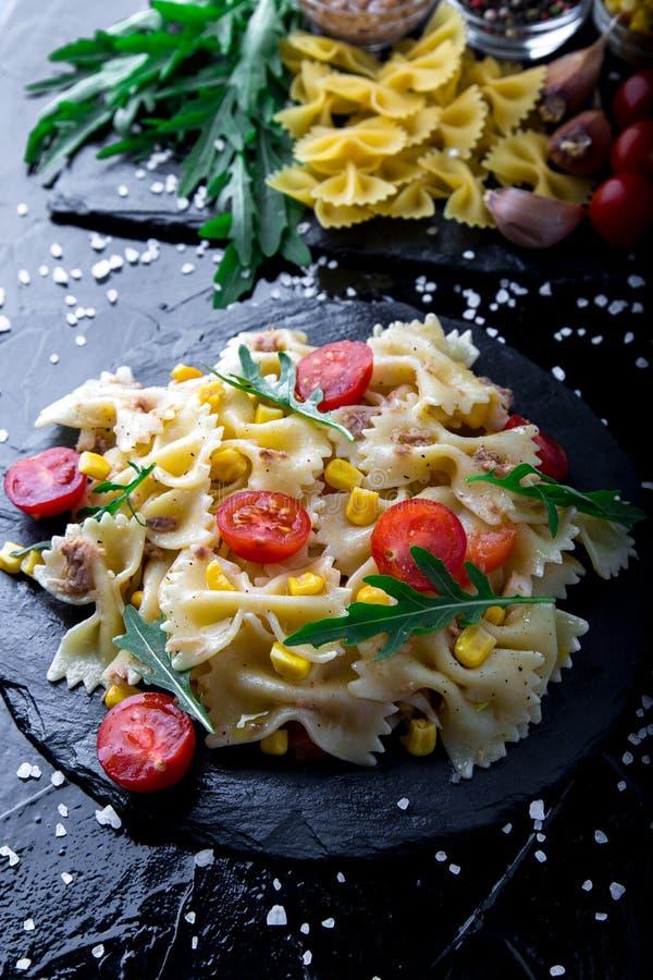 Pastasallad kritiserar in plattan med tomater körsbär, tonfisk, havre och arugula ingredienser italienska matlagningmatingrediens royaltyfri bild