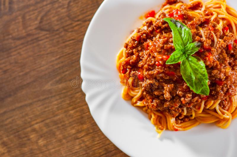 Pastaspagetti bolognese i den vita plattan på trätabellbakgrund royaltyfria bilder