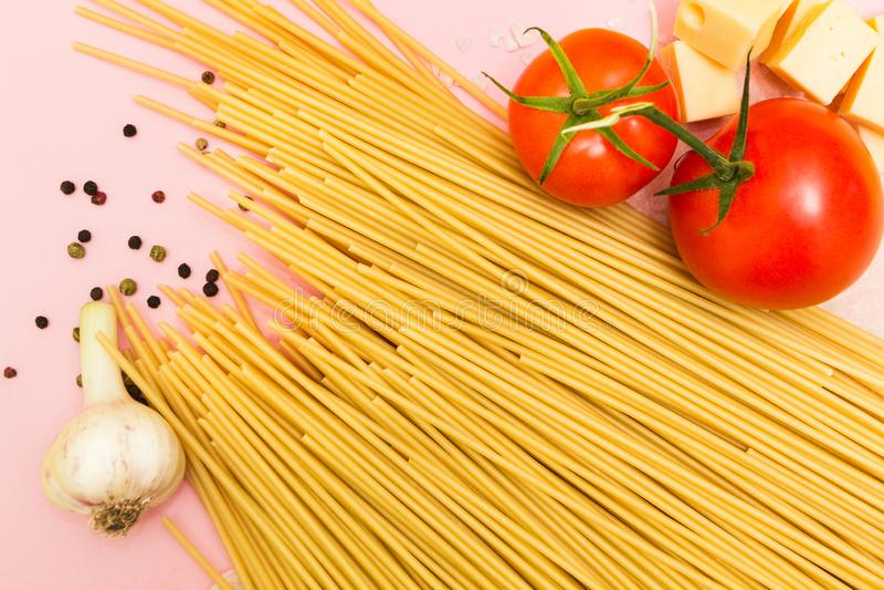 Pastaspagetti, grönsaker och kryddor, på rosa bakgrund arkivbilder