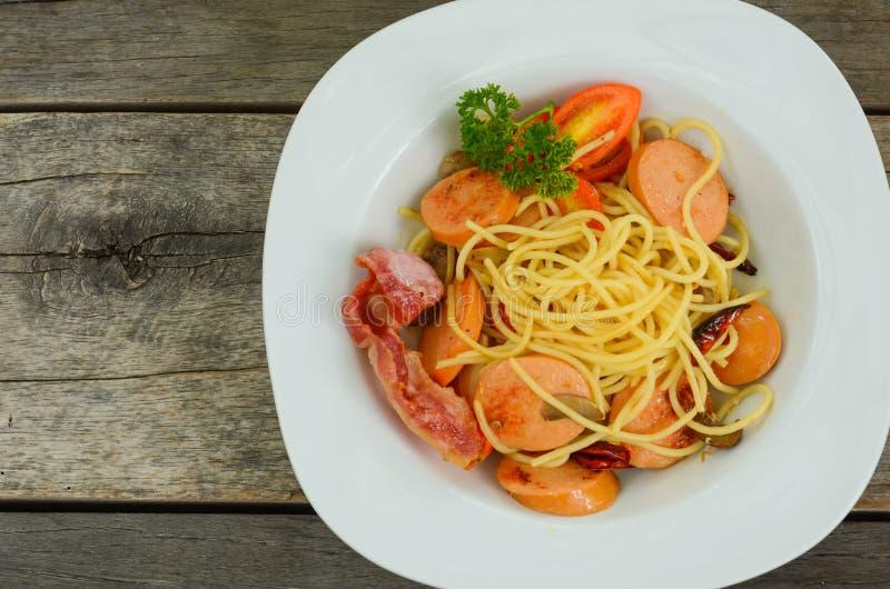Pastaspagetti med den stekte korven i den vita plattan p? tr?tabellbakgrund arkivfoto