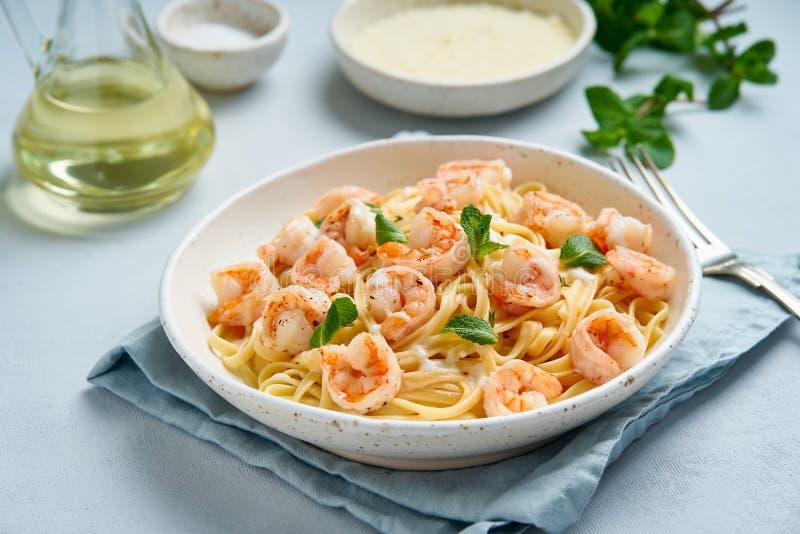 Pastaspagetti med grillade räkor, bechamelsås, mintkaramellblad på den blåa tabellen, italiensk kokkonst, sidosikt royaltyfria bilder