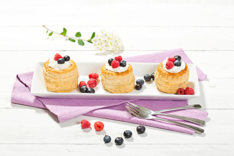 Paste sfoglia con vaniglia-gelato e crema, mirtilli e r fotografia stock
