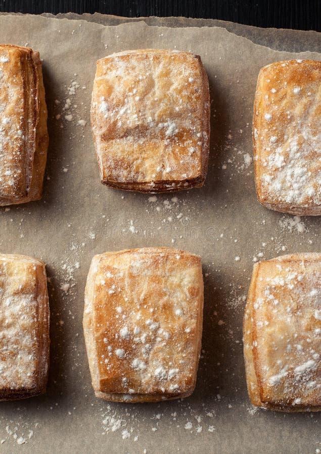 Paste sfoglia su una carta per cuocere con lo zucchero in polvere, vista superiore, verticale fotografie stock libere da diritti
