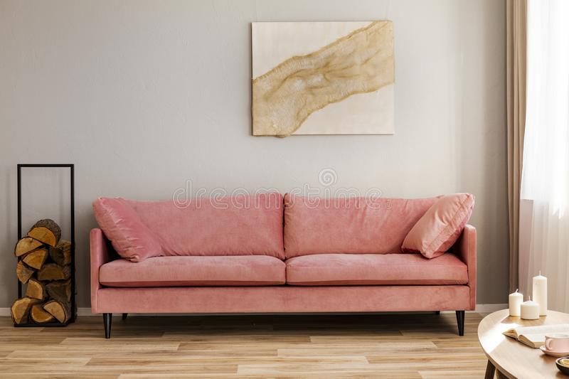 Pastel abstract painting on beige wall behind velvet pink settee in simple living room stock photography