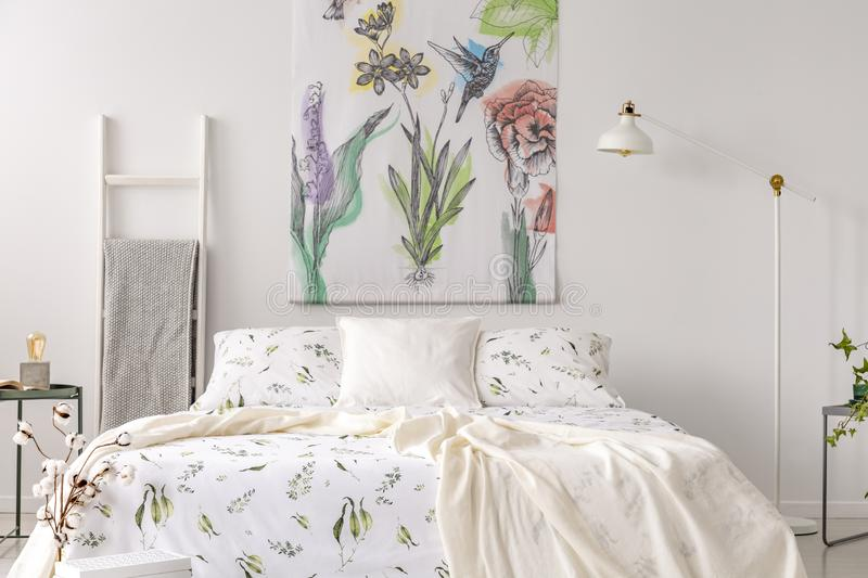 A pastel bedroom interior with a bed dressed in green plants pattern white linen. Fabric painted in flowers and birds on the backg stock photos