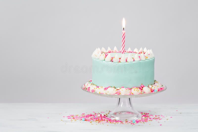 Pastel Blue Birthday Cake over White Background. stock photography