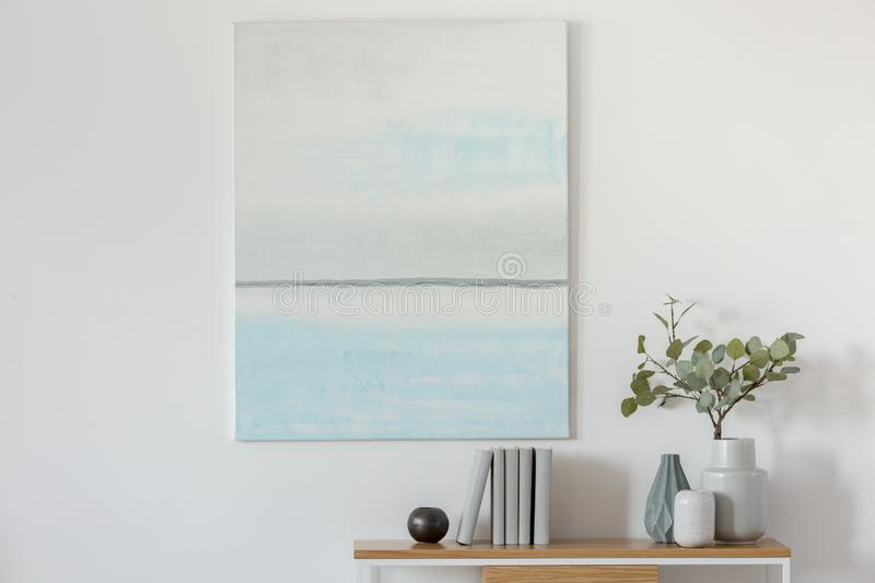Pastel blue and abstract oil painting on empty white wall with console table with flowers in vase and books stock photos