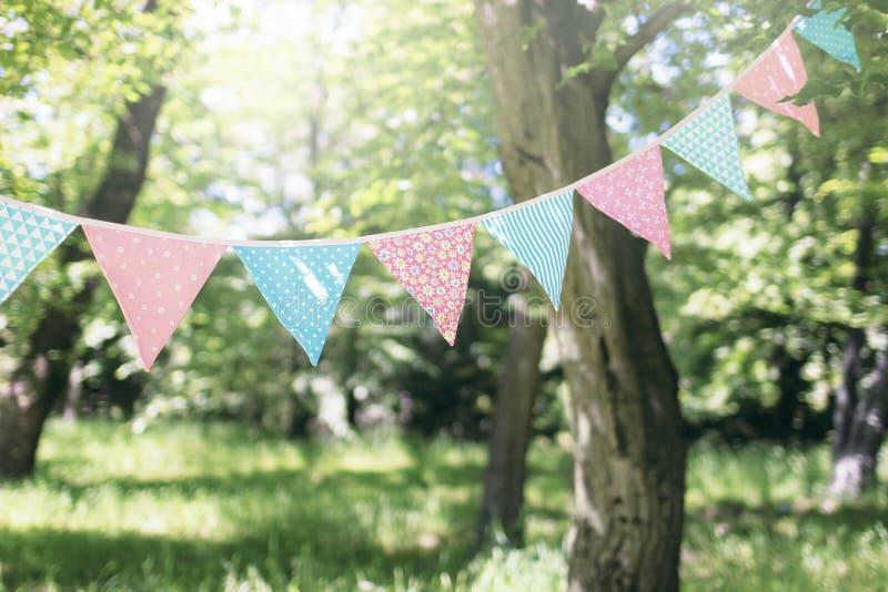 Pastel bunting flags hanging among trees. Summer garden party. Outdoor birthday, wedding decoration. Midsummer, festa stock image