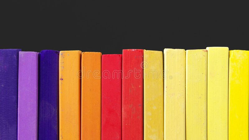 Pastel Chalk. A row of pastel chalk in front of dark background stock image
