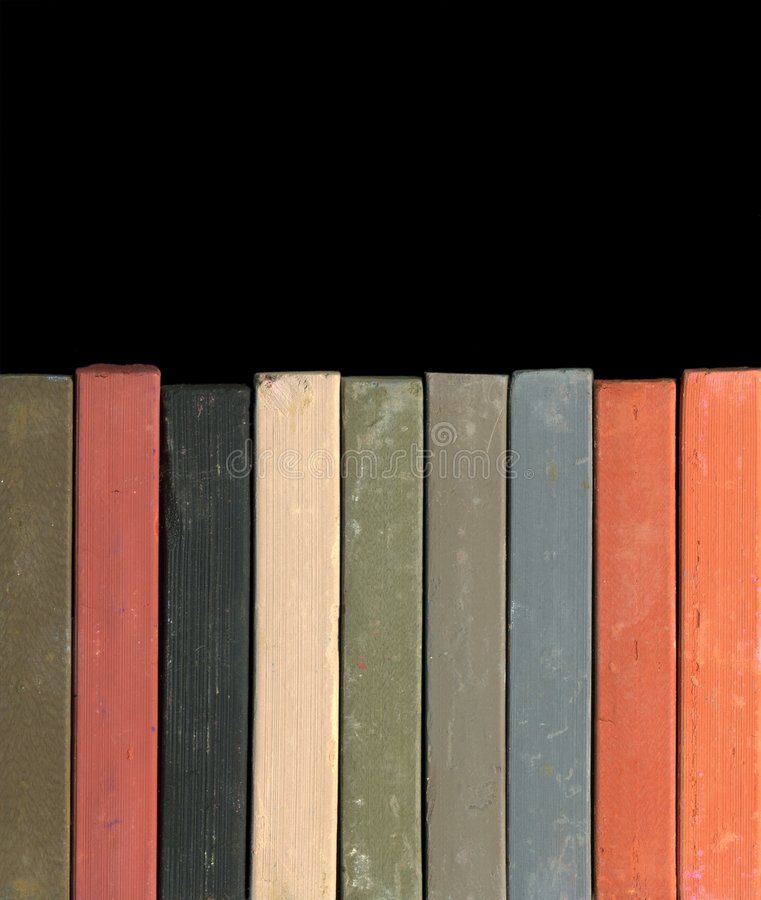 Pastel Chalk. A row of pastel chalk in front of dark background stock photo