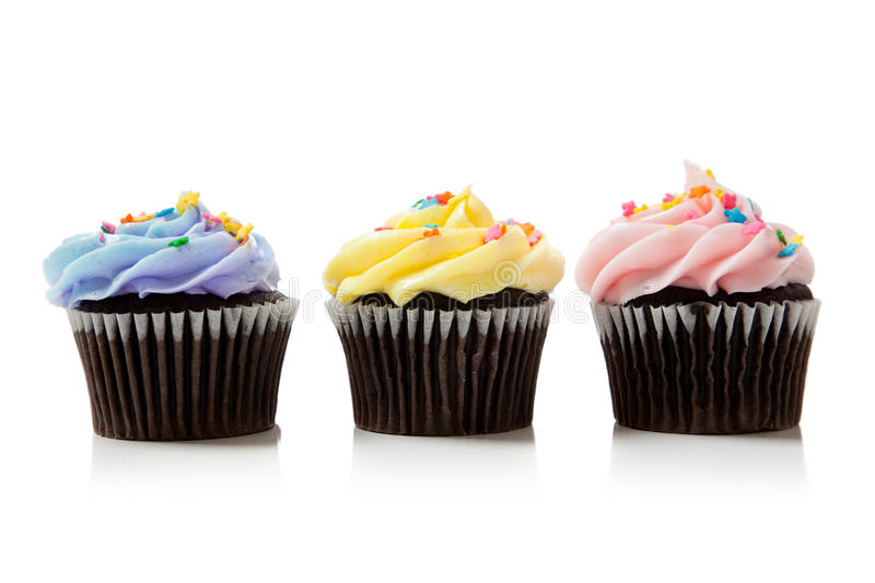 Pastel chocolate cupcakes on white. Pastel chocolate cupcakes including pink, blue and yellow on white stock photo