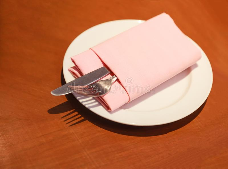 Pastel cloth napkin serviette folding with cutlery knife, fork, silverware in white plate prepared on the wooden table, ready. For customer to use. Hotel stock image